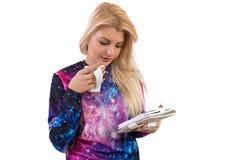 La muchacha lee el libro y bebe el café Imagen de archivo