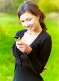 La muchacha lee sms en el teléfono móvil Fotografía de archivo