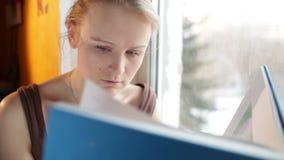 La muchacha lee un libro cerca de ventana. Ciérrese encima del retrato con la luz natural y el reflector. almacen de metraje de vídeo