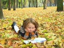 La muchacha lee un libro en el parque del otoño Imágenes de archivo libres de regalías
