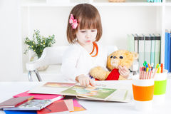 La muchacha lee un libro ilustrado a un oso de peluche Imagen de archivo