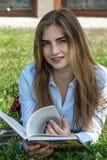 La muchacha lee un libro mientras que miente en la hierba Imágenes de archivo libres de regalías