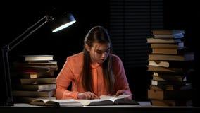 La muchacha lee y escribe la información en un cuaderno Fondo negro metrajes