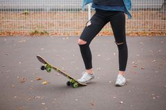 La muchacha levantó un patín con un pie en un parque del patín Fotografía de archivo libre de regalías