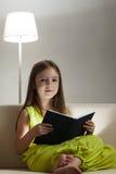 La muchacha leyó el libro en el sofá Foto de archivo