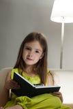 La muchacha leyó el libro en el sofá Imagenes de archivo