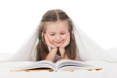 La muchacha leyó un libro en cama Fotos de archivo libres de regalías