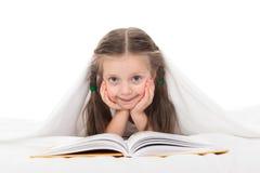 La muchacha leyó un libro en cama Foto de archivo