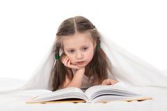 La muchacha leyó un libro en cama Imágenes de archivo libres de regalías