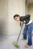 La muchacha limpia a casa con una mirada cansada Foto de archivo