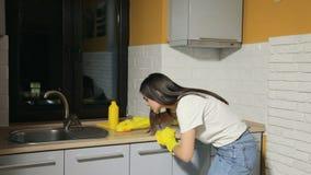 La muchacha limpia la cocina almacen de metraje de vídeo