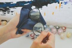 La muchacha limpia los vidrios con la servilleta Foto de archivo libre de regalías
