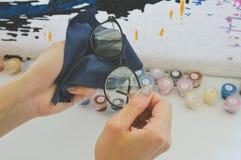 La muchacha limpia los vidrios con la servilleta Imagen de archivo
