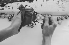 La muchacha limpia los vidrios con la servilleta Fotos de archivo libres de regalías