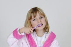 La muchacha limpia sus dientes Fotos de archivo