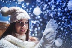 La muchacha linda adorna el árbol de navidad con las bolas Imagen de archivo