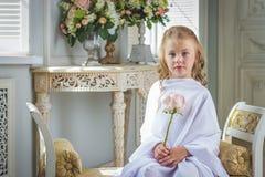 La muchacha linda alegre que se sentaba con subió Imagen de archivo libre de regalías