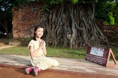 La muchacha linda asiática con el respeto o ruega, los wi entrelazados cabeza de Buda foto de archivo