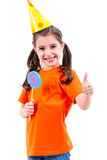 La muchacha linda con el caramelo coloreado que muestra los pulgares sube gesto Imagenes de archivo