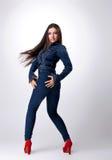 La muchacha linda con el pelo largo en pantalones vaqueros se viste Imagenes de archivo