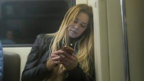 La muchacha linda con el pelo rubio largo en la chaqueta de cuero endereza el artilugio del uso en metro Imagen de archivo