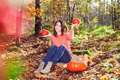 La muchacha linda con la calabaza y el maíz en otoño hermoso parquean en sunn Imagen de archivo