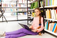 La muchacha linda con la trenza sostiene el ordenador portátil en biblioteca Imágenes de archivo libres de regalías