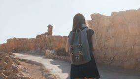 La muchacha linda con la mochila camina a lo largo de ruinas antiguas El turista femenino bastante europeo explora la fortaleza d metrajes