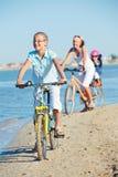 La muchacha linda con su madre y el hermano montan las bicis Imagen de archivo libre de regalías