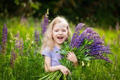 La muchacha linda con un ramo de lupine púrpura florece foto de archivo