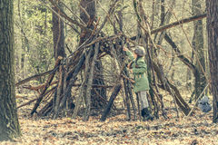La muchacha linda de Ittle construye una choza en el bosque Imagen de archivo libre de regalías