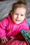 La muchacha linda de ojos azules en un suéter rosado ríe fotografía de archivo
