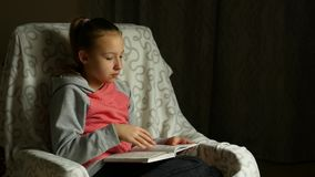 La muchacha linda del niño en camiseta rosada gris se sienta en silla cómoda en sitio y lee el libro almacen de video