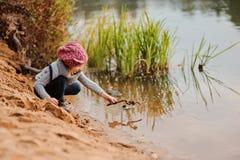 La muchacha linda del niño en rosa hizo punto juegos del sombrero con el palillo en lado del río con la playa de la arena fotos de archivo