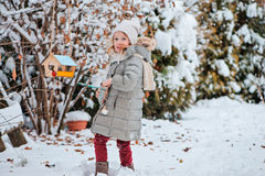 La muchacha linda del niño pone las semillas en alimentador del pájaro en jardín nevoso del invierno Foto de archivo libre de regalías