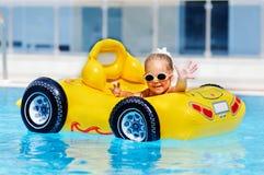 La muchacha linda del niño se divierte en la piscina al aire libre Fotos de archivo