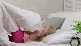 La muchacha linda del pequeño niño despierta de sueño en cama