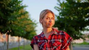 La muchacha linda del retrato con el pelo blanco largo en camisa a cuadros roja es dudas y miradas fijas en la cámara almacen de metraje de vídeo