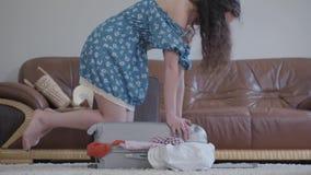 La muchacha linda del retrato está intentando cerrar la maleta que se sienta en ella Mujer rizada que embala una maleta antes de  almacen de metraje de vídeo