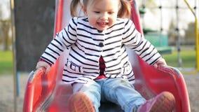 La muchacha linda divertida con dos colas de caballo está jugando en diapositiva roja Niño femenino feliz en la chaqueta rayada q metrajes