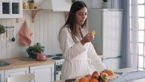 La muchacha linda en la albornoz blanca come la rebanada de naranja en cocina, cámara lenta metrajes