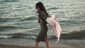 La muchacha linda en capa del otoño camina a lo largo de la playa en la puesta del sol muchacha que presenta para la cámara al ai metrajes
