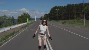La muchacha linda en pantalones cortos y tops patina SMI en pcteres de ruedas en el camino Fotografía de archivo libre de regalías
