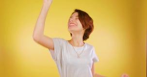 La muchacha linda en un baile divertido del fondo amarillo de la felicidad, disfruta la victoria Ganador, lotería, movimientos di almacen de video