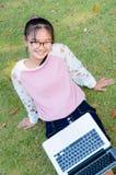 La muchacha linda es feliz con el cuaderno en hierba Fotos de archivo