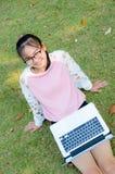 La muchacha linda es feliz con el cuaderno en hierba Imagen de archivo libre de regalías
