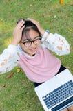 La muchacha linda es feliz con el cuaderno en hierba Imagenes de archivo