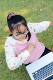 La muchacha linda es feliz con el cuaderno en hierba Imágenes de archivo libres de regalías