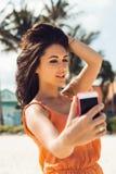 La muchacha linda hace el selfie en la playa tropical Imágenes de archivo libres de regalías