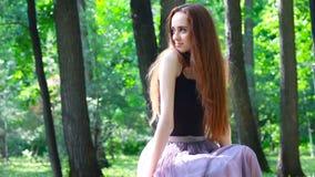 La muchacha linda hermosa se sienta en el parque del verano metrajes
